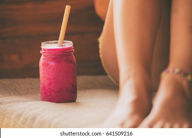 Woman relaxing and drinking smoothie outdoors.
