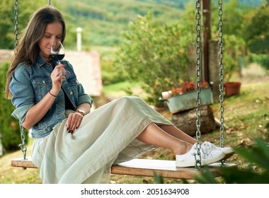 Woman relaxing drinking tasting red wine outdoor in garden. Authentic and atmospheric moment.