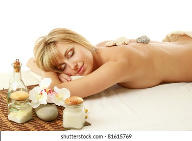 A woman relaxing during a stone therapy on white background