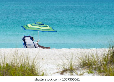 Woman Relaxing and Enjoying a Beautiful Sunny Day at the Beach.