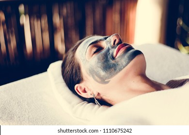 Woman relaxing with a facial mask at the spa