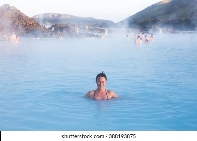 Woman relaxing in geothermal spa in hot spring pool in Iceland. Girl enjoying bathing in a blue water lagoon with famous healing mud.