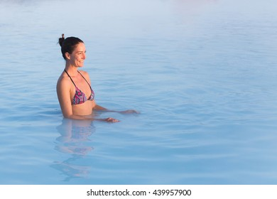 Woman relaxing in geothermal spa in hot spring pool in Iceland. Girl enjoying bathing in a blue water lagoon.