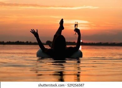 Woman relaxing with a glass of champagne on inflatable ring in water on the sunset