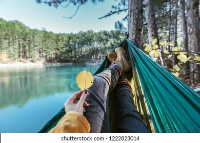 Woman relaxing in the hammock by the lake in the autumn forest, POV view of legs in trekking boots. Hiking in fall. Wanderlust concept scene.