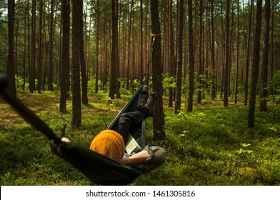 Woman relaxing in the hammock in the middle of a forest, watching blue sky and pine trees. Slow life concept. Hipster. Yellow mustard hat, spring green colors.