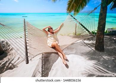 Woman is relaxing in a hammock on the beach among the palm near the sea. Tanzania, island Zanzibar.