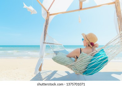 Woman relaxing in hammock on the beach,Summer vacation and travel concept
