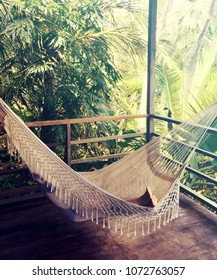 woman relaxing in a hammock on a beautiful patio surrounded by lush jungle, Panama