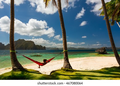 Woman relaxing in hammock on Pinagbuyutan island, near Palawan, Phillipines