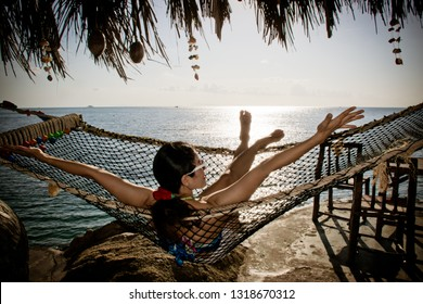 Woman relaxing in the hammock on tropical beach, hot sunny day.Soft focus