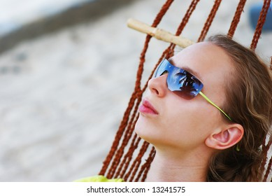 Woman relaxing in hammock on the tropical beach. Sky & palms reflection in sunglasses.