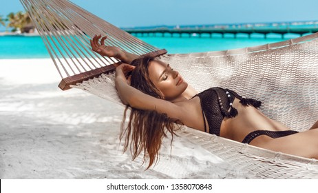 Woman relaxing in the hammock on tropical beach, summer vaction. Free girl chilling on exotic island.