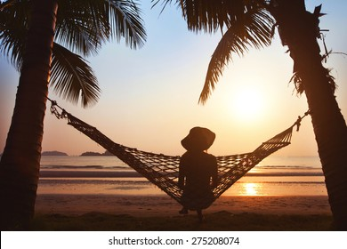 woman relaxing in hammock at sunset on the beach, enjoy the life