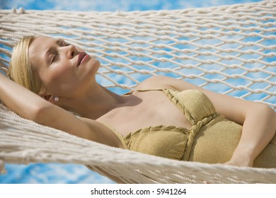 Woman relaxing in a hammock with water behind