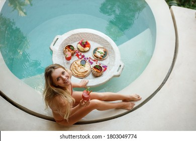Woman relaxing and having floating breakfast in jungle pool on luxury villa in Bali, look at th camera and smiing