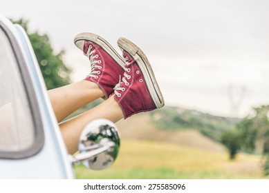 Woman relaxing in her car while driving in the countryside - Young  cool girl with shoes out of the automobile window to enjoy the view