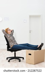 Woman relaxing in her new home or office sitting in an office chair with her feet up on a cardboard packing carton