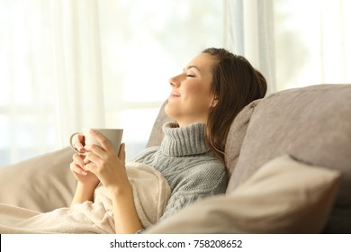 Woman relaxing holding a coffee mug sitting on a sofa in the living room in a house interior