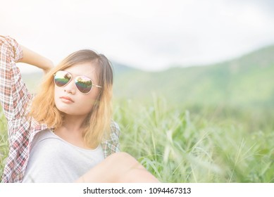 woman relaxing holiday amidst meadows, mountains and sky.