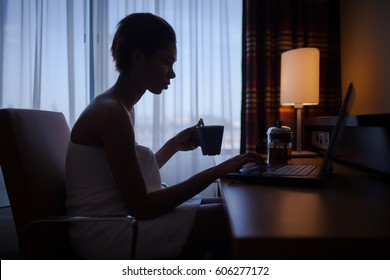 Woman relaxing at home after bath with laptop and cup of tea.