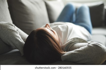 Woman relaxing at home laying on her back on a grey couch.