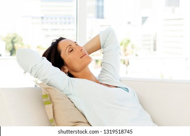 Woman relaxing at home on sofa - beautiful brunette closing eyes