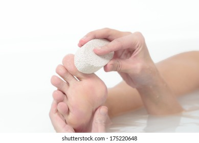 Woman relaxing in a hot soapy bath using a pumice stone to exfoliate her feet and remove dead skin cells from the sole in a personal hygiene and skincare concept
