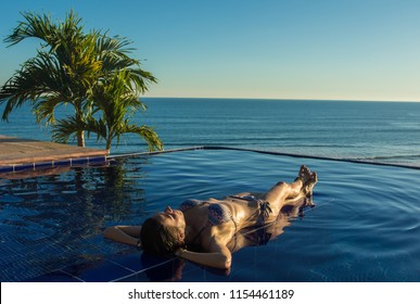 Woman relaxing in the infinity pool