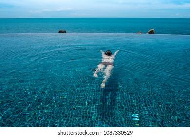 Woman Relaxing In Infinity Swimming Pool Water.
