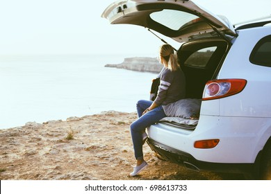 Woman relaxing inside car trunk and watching on sea. Fall trip in sunset. Freedom travel concept. Autumn weekend.
