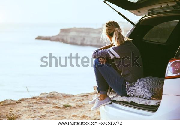 Mujer relajándose dentro del maletero de camión y viendo el mar. Paseo de otoño al atardecer. Concepto de viajes de libertad. Fin de semana de otoño.