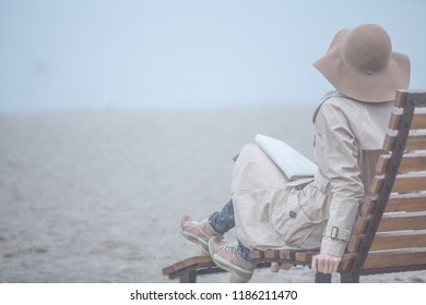 Woman relaxing and listening to sea on lonely autumn or winter beach wearing coat and felt hat