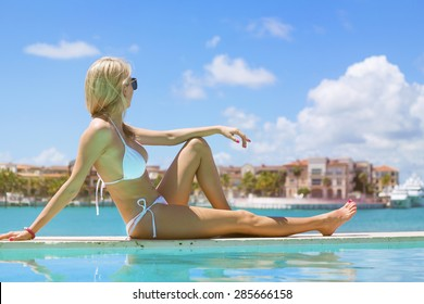 Woman relaxing and looking into distance by the pool