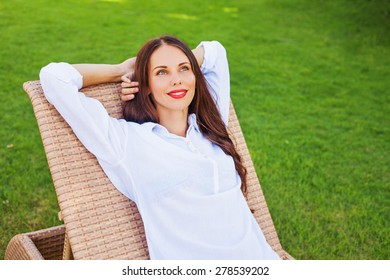 woman relaxing in a lounger over green grass