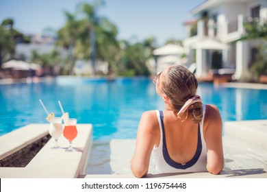 Woman relaxing at the luxury poolside. Girl at travel spa resort pool. Summer luxury vacation.
