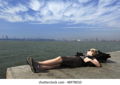 """woman relaxing at the """"marine drive"""" in Mumbai ( Bombay),India-  -- with the city skyline in the background. Photo taken with a wide-angle lens"""