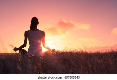 Woman relaxing meditating in grass field.