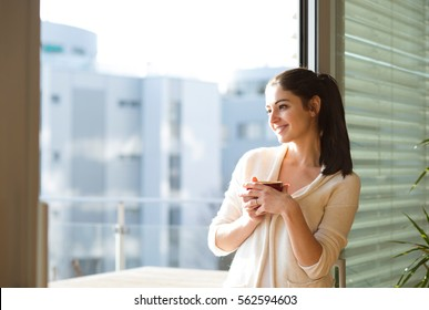Woman relaxing on balcony holding cup of coffee or tea