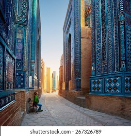 Woman relaxing on the bench and enjoying beauty of the ancient complex of Shah-i-Zinda, Samarkand, Uzbekistan