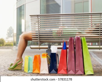 woman relaxing on bench outside shopping center. Horizontal shape, full length