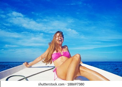 Woman relaxing on a boat and laughing