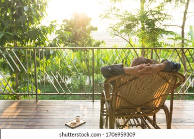 Woman relaxing on the chair at wooden balcony watching sunset  in the garden