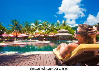 woman relaxing on a chaise lounge by the luxury pool
