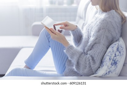 woman is relaxing on comfortable couch and using laptop at home