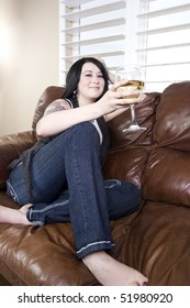 Woman Relaxing on the Couch with a Glass of Wine