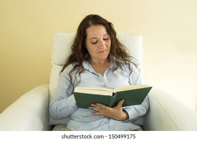woman relaxing on a couch reading a book on a couch