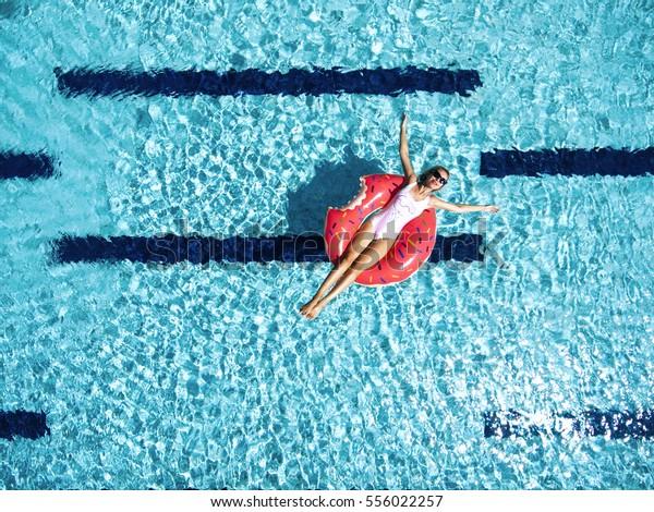Vrouw ontspannen op donut lilo in het zwembadwater op warme zonnige dag. Zomervakantie idyllisch. Bovenaanzicht.
