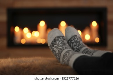 Woman relaxing on fuzzy rug against blurred background, closeup. Winter atmosphere