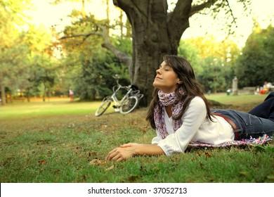 woman relaxing on grass field after a bike ride